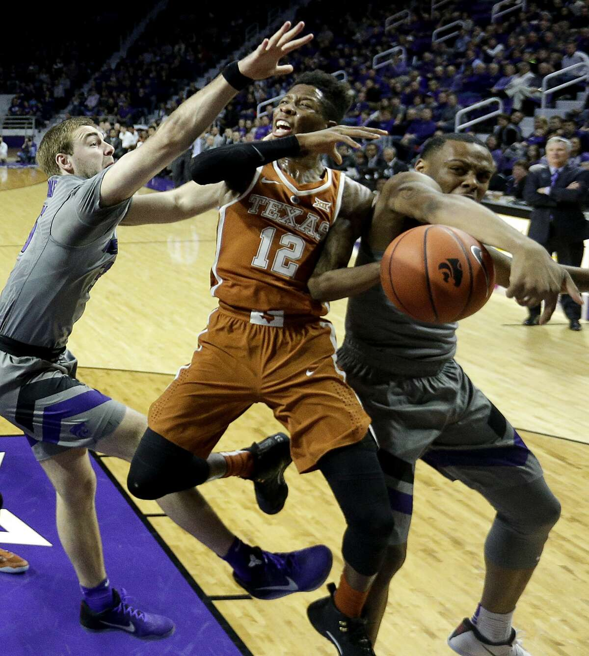 Texas' Kerwin Roach Jr. (12) is pressured by Kansas State's Austin Budke, left, and Carlbe Ervin II, right, as he puts up a shot during the first half of an NCAA college basketball game Friday, Dec. 30, 2016, in Manhattan, Kan. (AP Photo/Charlie Riedel)