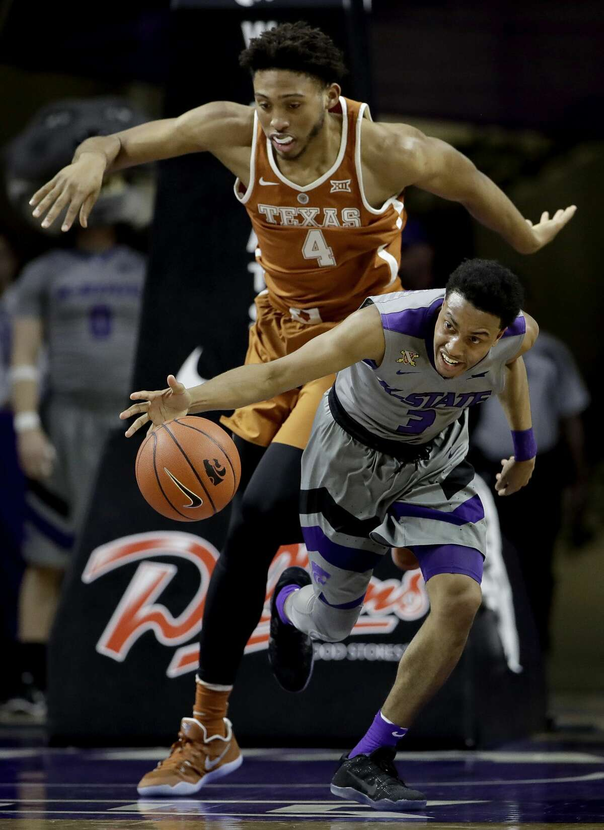 Kansas State's Kamau Stokes (3) beats Texas' James Banks (4) to a loose ball during the second half of an NCAA college basketball game Friday, Dec. 30, 2016, in Manhattan, Kan. Kansas State won 65-62. (AP Photo/Charlie Riedel)