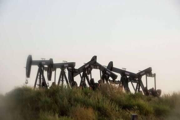 Six pumpjacks stand outside of Cotulla, Texas in the Eagle Ford Shale region on August 6, 2015. The plunge in oil prices in the past six months has forced drilling and oil service companies to fire workers and idle rigs throughout the Eagle Ford Shale area.