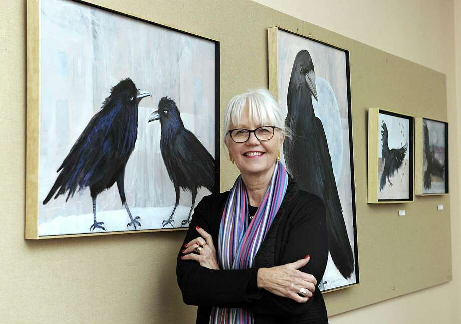 "Jo-Ann Cordes with a display of her mixed-media work, ""Ravens,"" on display at the Bethel Public Library until the end of January. Photo: Carol Kaliff / Hearst Connecticut Media / The News-Times"