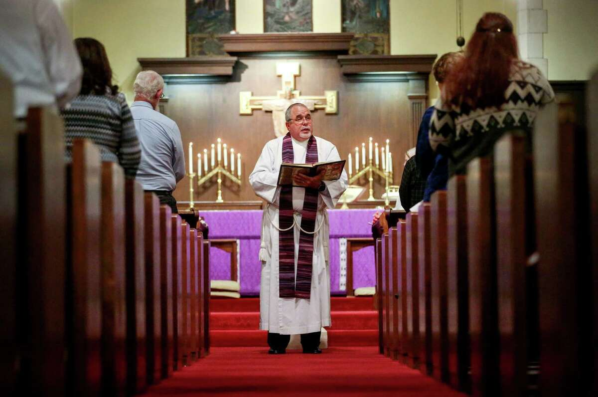 Keith Giblin, a magistrate judge and Episcopal priest, reads a passage from the Bible during a service at St. Paul's Episcopal Church in Orange.