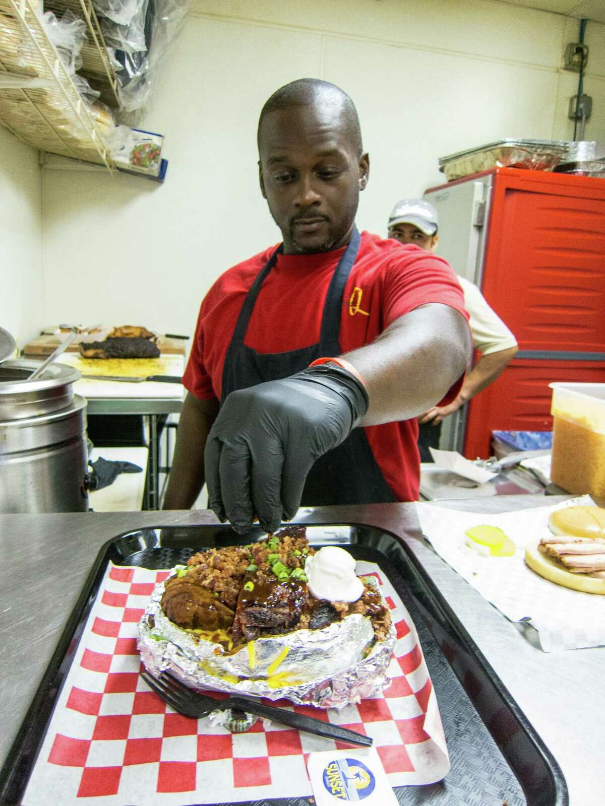 Pitmaster Steve Garner puts the finishing touches (bacon) on the Big Poppa baked potato at Southern Q. Qualified applicants for important kitchen positions are on pitmasters' wish lists.