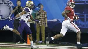 Alabama running back Bo Scarbrough (9) looks back as he runs for a touchdown against Washington defensive back Kevin King (20) during the second half of the Peach Bowl NCAA college football playoff game, Saturday, Dec. 31, 2016, in Atlanta. (AP Photo/David Goldman)