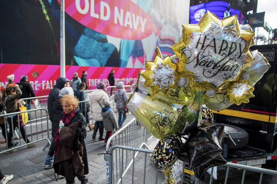 Pedestrians walk past New Years celebration balloons hanging on a metal barricade, Friday, Dec. 30, 2016, in New York's Times Square. Photo: Mary Altaffer, AP / Copyright 2016 The Associated Press. All rights reserved.