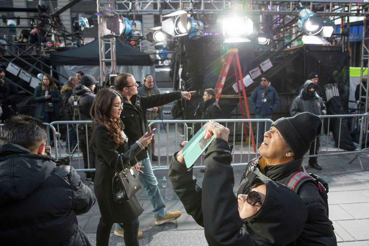Visitors to Times Square take photos as technicians prepare a stage that will be used in the New Years celebration, Friday, Dec. 30, 2016, in New York's Times Square.