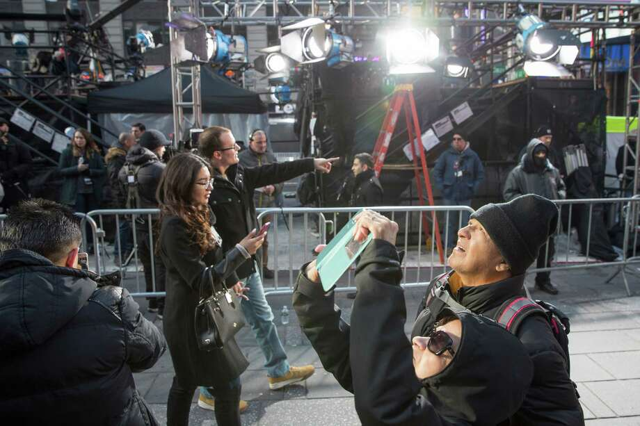 Visitors to Times Square take photos as technicians prepare a stage that will be used in the New Years celebration, Friday, Dec. 30, 2016, in New York's Times Square. Photo: Mary Altaffer, AP / Copyright 2016 The Associated Press. All rights reserved.