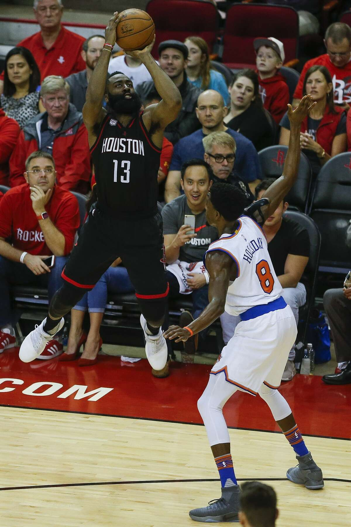 Houston Rockets guard James Harden (13) takes a shot as New York Knicks guard Justin Holiday (8) is called for a foul as the Houston Rockets take on the New York Knicks at the Toyota Center Saturday, Dec. 31, 2016 in Houston. ( Michael Ciaglo / Houston Chronicle )