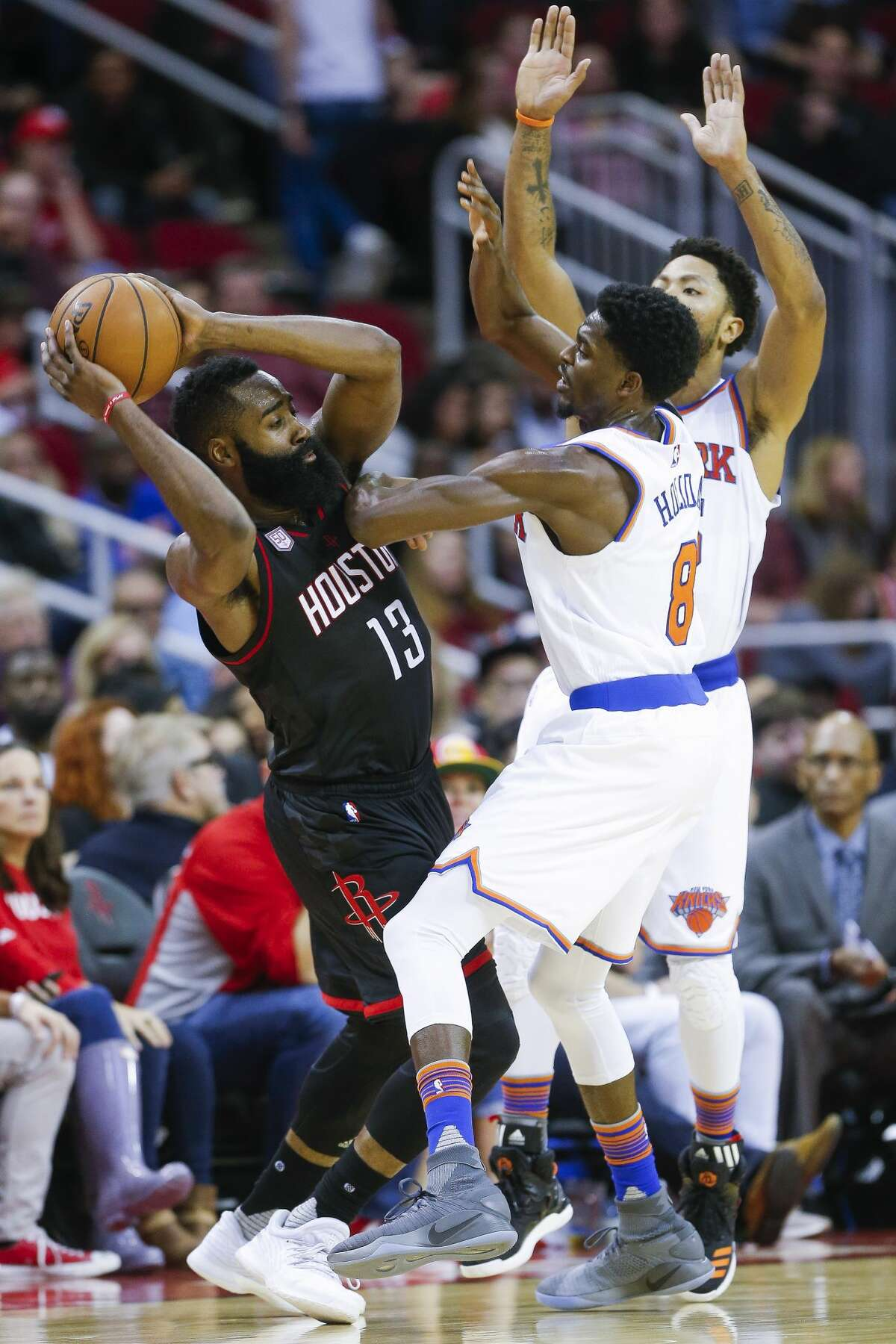 Houston Rockets guard James Harden (13) looks to make a pass around New York Knicks guard Justin Holiday (8) and guard Derrick Rose (25) as the Houston Rockets take on the New York Knicks at the Toyota Center Saturday, Dec. 31, 2016 in Houston. ( Michael Ciaglo / Houston Chronicle )