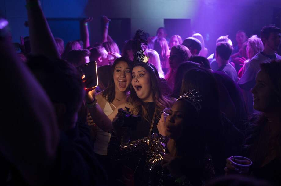 BRITTNEY LOHMILLER   blohmiller@mdn.net Hayley Jacobs, left, of Bay City takes a photo with Meghan Samyn of Essexville while dancing during Midnight on Main at Dow Diamond Sunday evening. Photo: Brittney Lohmiller/Midland Daily News/Brittney Lohmiller