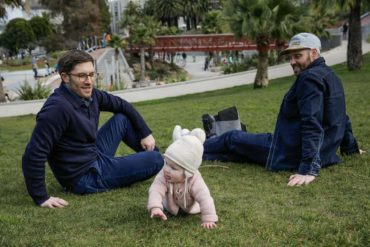 Parents Andres Power (left) and Rod Hipskind (right) watch their daughter Inez Hipskind Power (center), 8 months, crawl in the grass while playing in Dolores Park in San Francisco, Calif., on Saturday, Dec. 31, 2016.