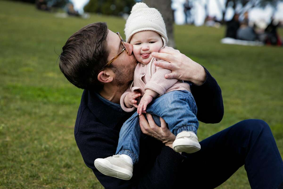 Andres Power gives his daughter Inez Hipskind Power (center), 8 months, a kiss while playing in Dolores Park in San Francisco, Calif., on Saturday, Dec. 31, 2016.