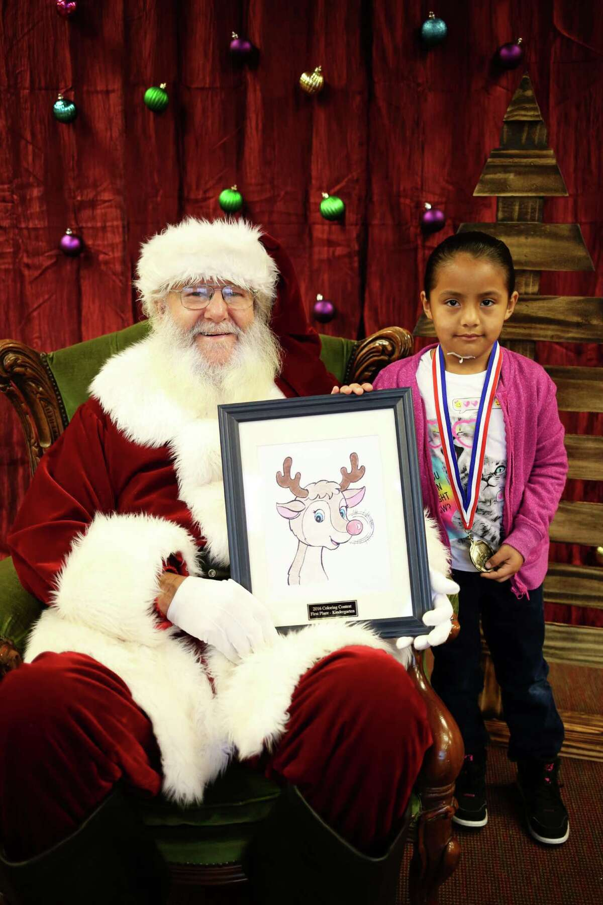 Jocelyn Escoto, pictured with Santa, won first place in the kindergarten grade division of the Hometown Christmas Coloring Contest.