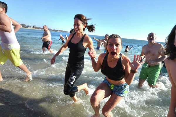 Marni Lane and Rhodie Lenz from Westport run out of the water after a jump into a cold Long Island Sound on New Year's Day at Compo Beach in Westport, during the 2017 Temple Israel 10th Anniversary Polar Bear Plunge. Around 100 peolple took the plunge and have raised so far 56 thousand dollars  for many different charities. Including Interfaith Housing, Marfan Foundation, Autism Speaks, PanCan, Hole in the Wall Gang, Make a Wish, United Cerebral Palsy, in Westport Conn. on Sunday January 1, 2017