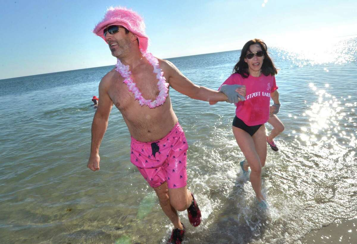Steve Snow from Fairfield who raised 20 thousand dollars for breast cancer research foundation in memory of his mother in law emerges with wife Jen and daughter Simone from Long Island Sound on New Year's Day at Compo Beach in Westport, during the 2017 Temple Israel 10th Anniversary Polar Bear Plunge. Around 100 peolple took the plunge and have raised so far 56 thousand dollars for many different charities. Including Interfaith Housing, Marfan Foundation, Autism Speaks, PanCan, Hole in the Wall Gang, Make a Wish, United Cerebral Palsy, in Westport Conn. on Sunday January 1, 2017