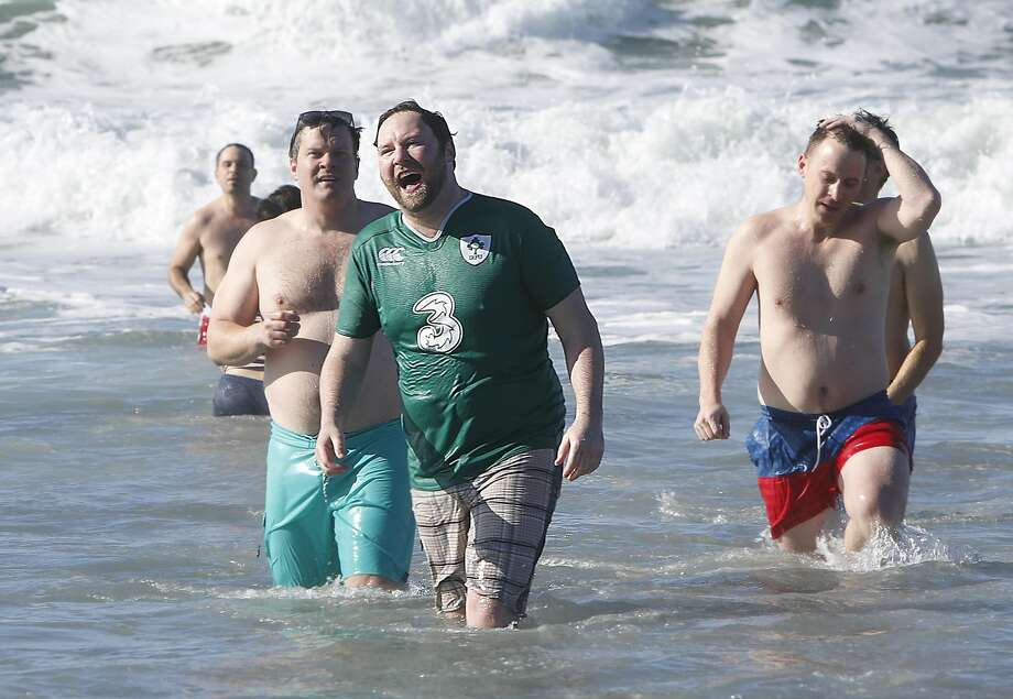 About a hundred people including Peter Byrne (in green shirt) from San Francisco joined in the New Year's Day Pacific Ocean Plunge & After Party  at Ocean Beach at noon on Sunday, January 1, 2017, in San Francisco, Calif. Photo: Liz Hafalia, The Chronicle