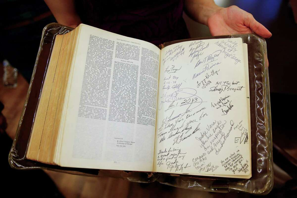 Ericka Gonzalez, daughter of Justice of the Peace, Precinct 1, Place 1 Richard Vara, shows off signatures in the family bible Vara has been sworn in with since he first took office in 1974. He used the bible again as he was sworn in at the historic 1910 Harris County Courthouse Sunday, Jan. 1, 2017 in Houston.