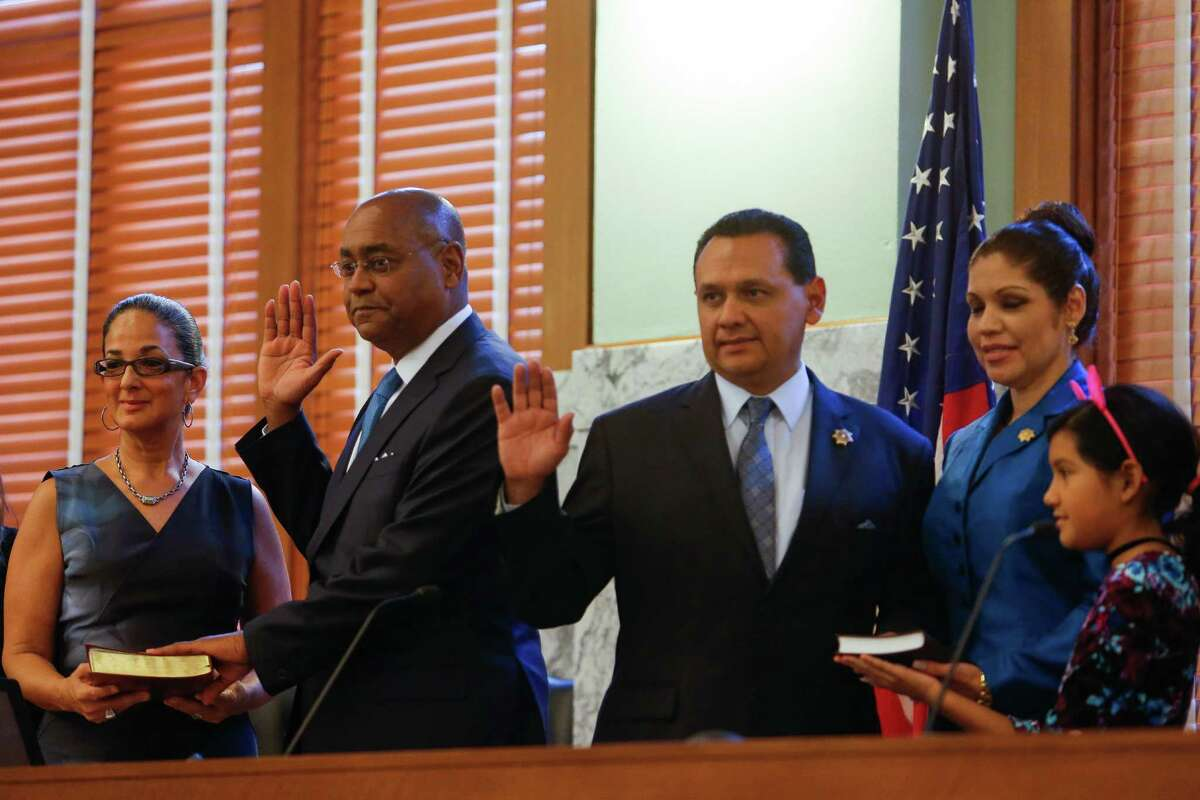 Harris County County Commissioner, Precinct 1 Rodney Ellis, second from left, and Harris County Sheriff Ed Gonzalez, center, are sworn in next to their families at the historic 1910 Harris County Courthouse Sunday, Jan. 1, 2017 in Houston.