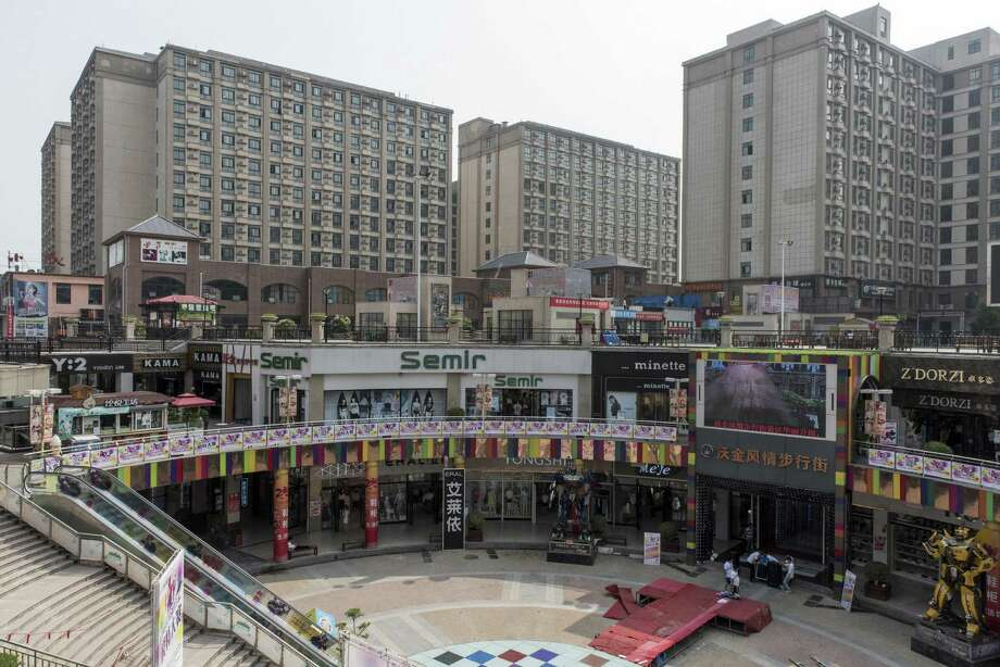 Dormitories for Foxxconn factory workers sit behind an open-air mall in Zhengzhou, China. A hidden bounty of perks, tax breaks and subsidies in Zhengzhou, home to the world's biggest iPhone factory, is core to the production of Apple's most profitable product, a New York Times investigation found. Photo: Gilles Sabrie /New York Times / NYTNS
