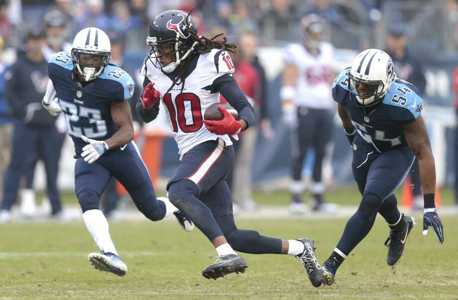 Houston Texans wide receiver DeAndre Hopkins (10) runs between Tennessee Titans cornerback Brice McCain (23) and inside linebacker Avery Williamson (54) after a reception during the third quarter of an NFL football game at Nissan Stadium on Sunday, Jan. 1, 2017, in Nashville. ( Brett Coomer / Houston Chronicle ) Photo: Brett Coomer/Houston Chronicle