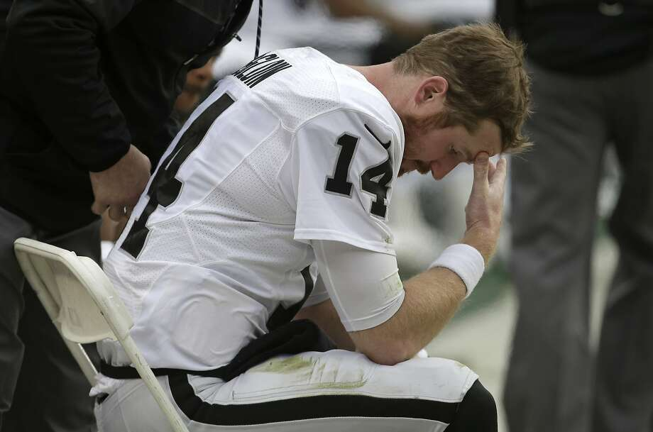 Quarterback Matt McGloin contemplates his shoulder injury on the sideline in the first half of the Raiders' loss in Denver. Photo: Joe Mahoney, Associated Press