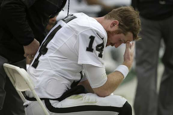 Oakland Raiders quarterback Matt McGloin sits on the sideline with an injury during the first half of the team's NFL football game against the Denver Broncos, Sunday, Jan. 1, 2017, in Denver. (AP Photo/Joe Mahoney)