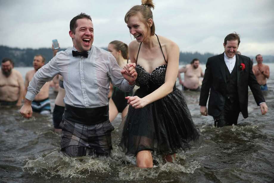 Scott Provence, left, Jo Landis, and Collin Provence, right, are dressed to the nines as they and several hundred other brave souls participate in the 15th annual Matthews Beach Polar Bear Plunge, Sunday, Jan. 1, 2017. Photo: SEATTLEPI.COM / SEATTLEPI.COM