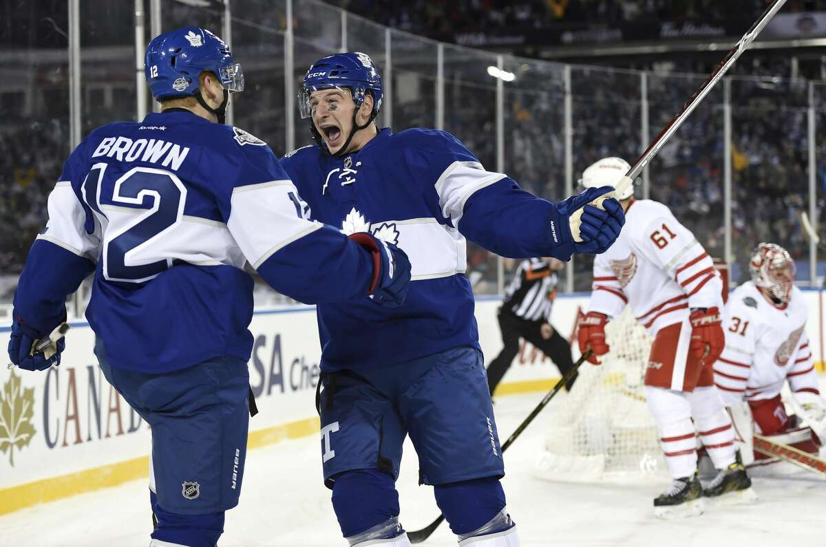 Toronto Maple Leafs right wing Connor Brown (12) celebrates his goal with teammate Zach Hyman (11) during the third period against the Detroit Red Wings in the NHL Centennial Classic hockey game in Toronto on Sunday, Jan. 1, 2017. (Frank Gunn/The Canadian Press via AP)