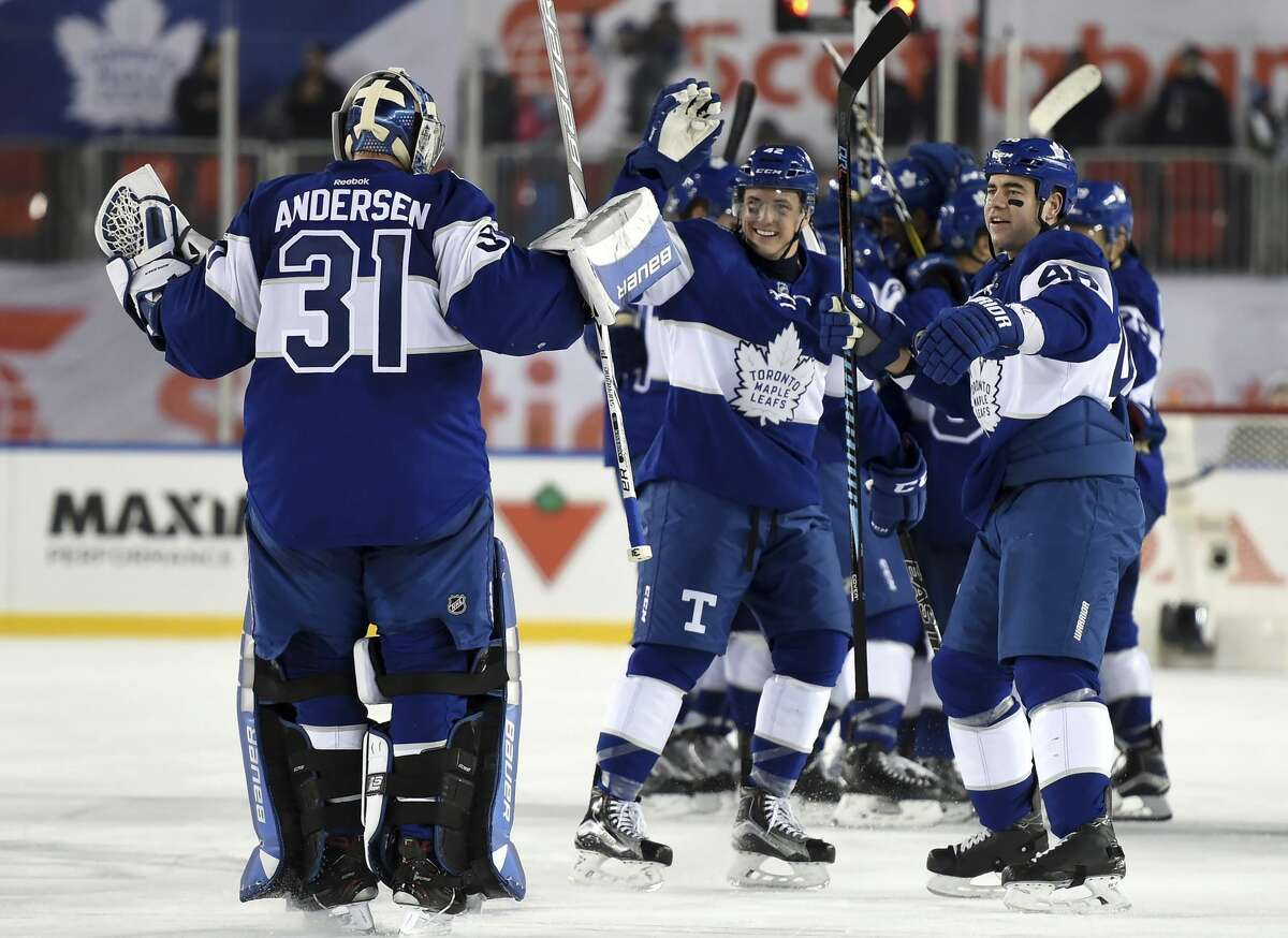 Toronto Maple Leafs goalie Frederik Andersen (31) celebrates with teammates Roman Polak (46) and Tyler Bozak (42) following overtime NHL Centennial Classic hockey action against the Detroit Red Wings, in Toronto, Sunday, Jan. 1, 2017. (Frank Gunn/The Canadian Press via AP)
