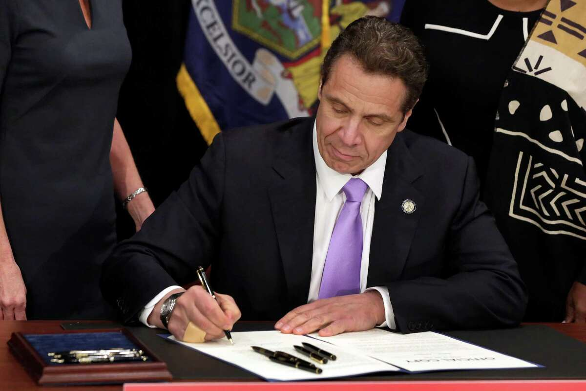 FILE- In this April 4, 2016 file photo, New York Gov. Andrew Cuomo signs a law that will gradually raise New York's minimum wage to $15, at the Javits Convention Center, in New York. New York joins 18 other states by raising its minimum wage in 2017. (AP Photo/Richard Drew, Pool, File)
