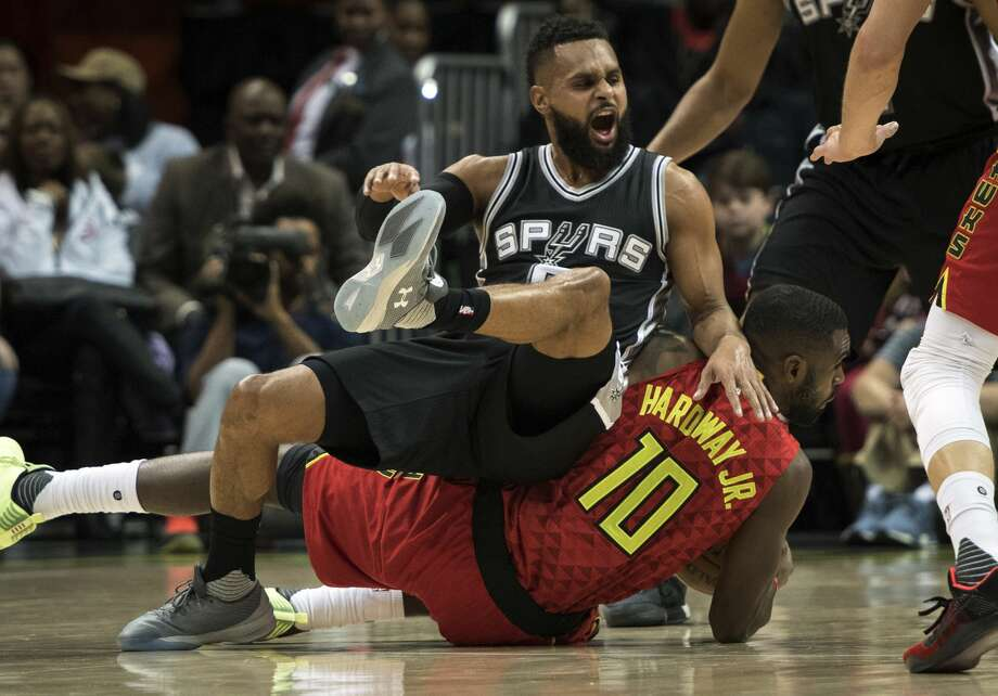 San Antonio Spurs guard Patty Mills, top, of Australia, falls on Atlanta Hawks guard Tim Hardaway Jr. while going for the ball during the first half of an NBA basketball game, Sunday, Jan. 1, 2017, in Atlanta. (AP Photo/John Amis) Photo: John Amis/Associated Press