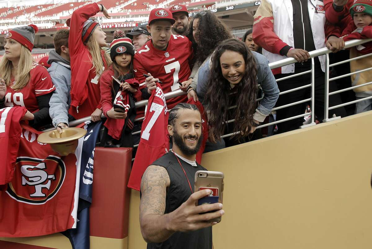 Colin Kaepernick (7) takes a picture with a fan before the San Francisco 49ers played the Seattle Seahawks at Levi's Stadium in Santa Clara, Calif., on Sunday, January 1, 2017.