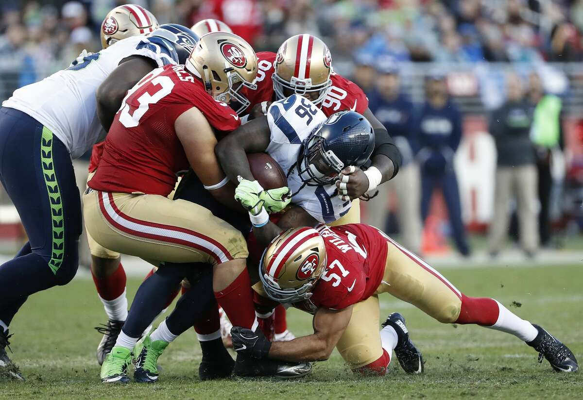 Seattle Seahawks running back Alex Collins (36) is tackled by San Francisco 49ers defensive tackle Chris Jones (93), nose tackle Glenn Dorsey (90) and linebacker Michael Wilhoite (57) during the second half of an NFL football game in Santa Clara, Calif., Sunday, Jan. 1, 2017. (AP Photo/Tony Avelar)