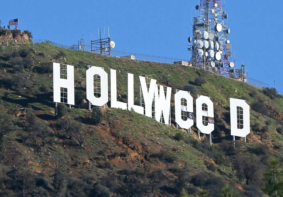 Los Angeles residents awoke New Year's Day to find a prankster had changed the famed Hollywood sign. Photo: Damian Dovarganes, STF / Damian Dovarganes