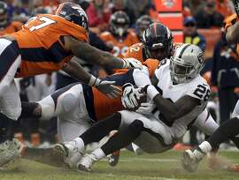 Oakland Raiders running back Latavius Murray (28) is tackled as he rushes against the Denver Broncos in the first half of an NFL football game, Sunday, Jan. 1, 2017, in Denver. (AP Photo/Joe Mahoney)