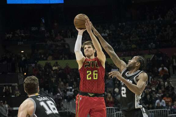 Atlanta Hawks guard Kyle Korver (26) shoots as San Antonio Spurs forward Kawhi Leonard (2) and San Antonio Spurs center Pau Gasol, of Spain, defend during overtime of an NBA basketball game, Sunday, Jan. 1, 2017, in Atlanta. Atlanta won 114-112. (AP Photo/John Amis)