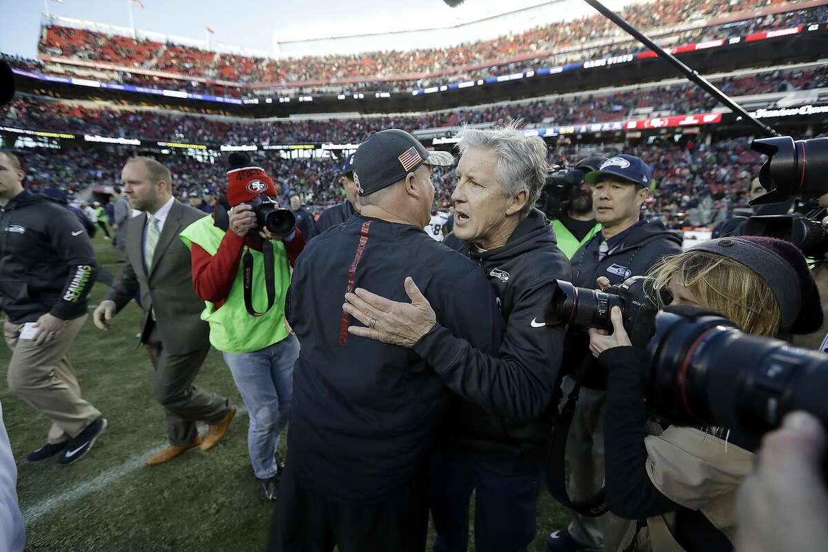 Seattle Seahawks head coach Pete Carroll, facing, hugs San Francisco 49ers head coach Chip Kelly after an NFL football game in Santa Clara, Calif., Sunday, Jan. 1, 2017. (AP Photo/Marcio Jose Sanchez)