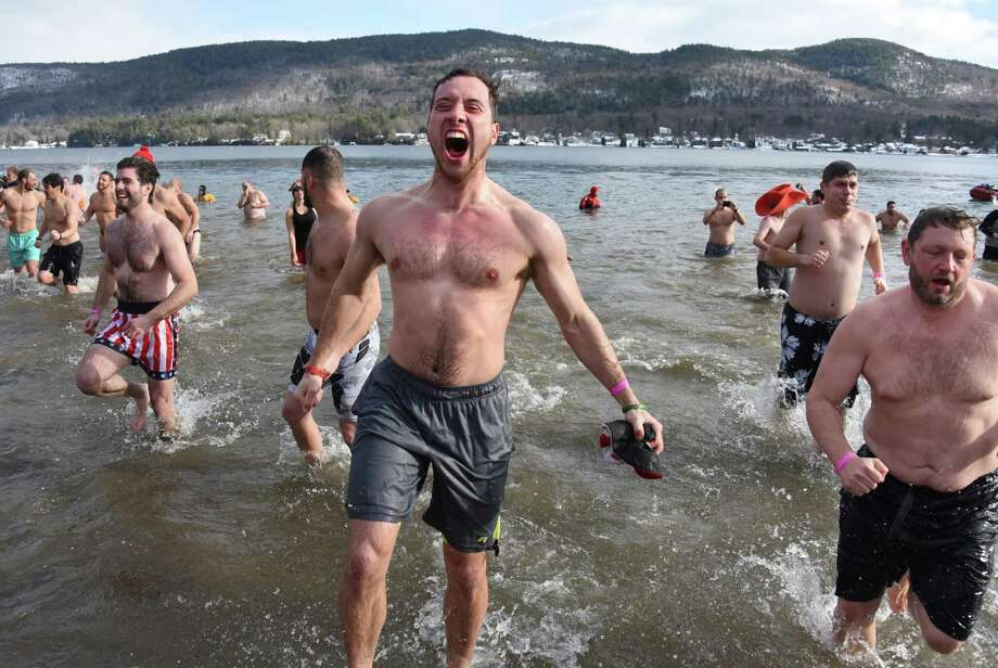 Ben Valentine of Rotterdam, center, screams as he runs in and out of the frigid waters of Lake George during the annual Polar Plunge at Shepard Park Beach on Sunday, Jan. 1, 2017 in Lake George, N.Y. (Lori Van Buren / Times Union) Photo: Lori Van Buren / 20039281A