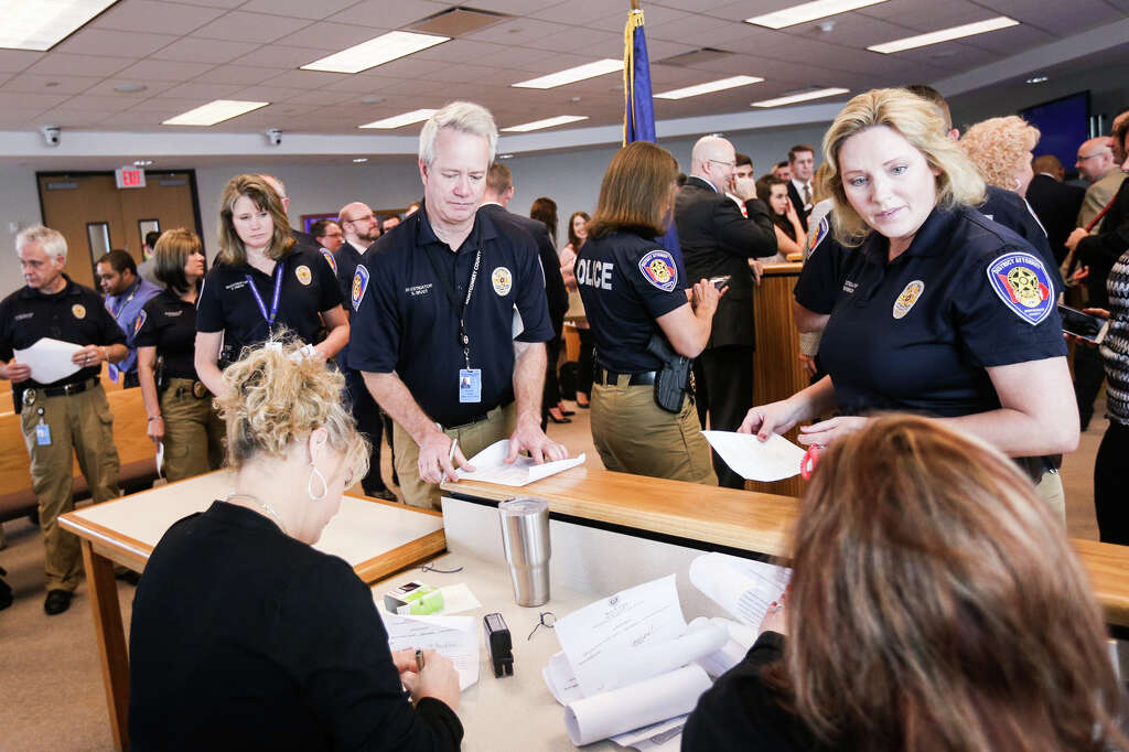 District attorney investigators line up to have their oaths notarized during the oath swearing ceremony on Sunday, Jan. 1, 2017, at the Alan B. Sadler Commissioners Court Building. Photo: Michael Minasi, Staff / © 2017 Houston Chronicle