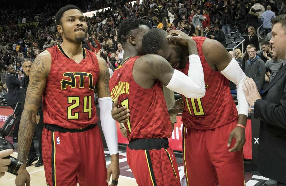 Atlanta Hawks guards Tim Hardaway Jr. (10) and Dennis Schroder, of Germany, congratulate each other as forward Kent Bazemore (24) watches after the team's NBA basketball game against the San Antonio Spurs, Sunday, Jan. 1, 2017, in Atlanta. Atlanta won 114-112 in overtime. (AP Photo/John Amis) Photo: John Amis/Associated Press