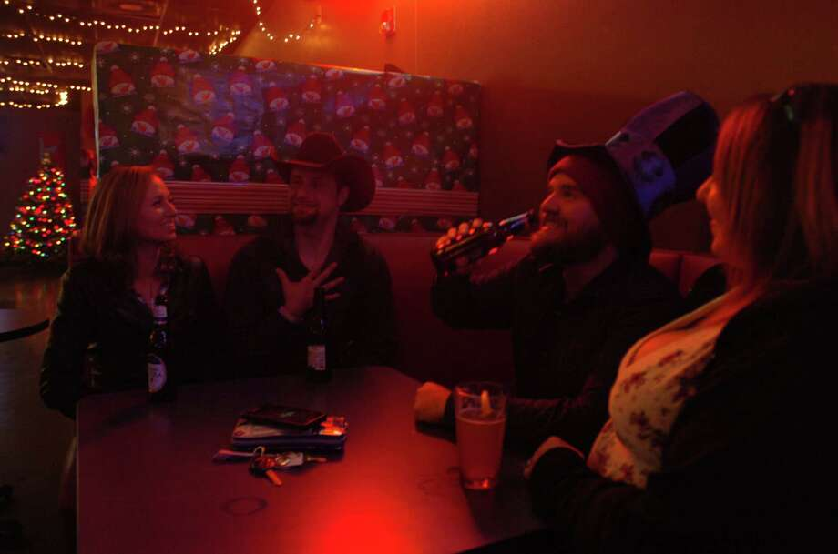 From left to right: Kristian Riley, 29, Kent Riley, 29, Dustin Desabier, 30, and Crystal Desabier, 33. They are celebrating Dustin's birthday at the bar, and the bar donned him with a purple Mad Hatter. Photo: Brooks Kubena
