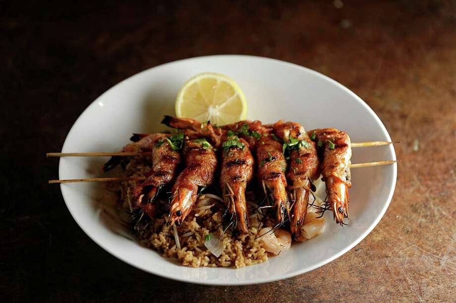 The Trung Sisters: shrimp wrapped with Thai basil, onions and bacon served over shrimp fried rice topped with lemon butter at Maba Pan-Asian Diner.  Photo: James Nielsen, Houston Chronicle / © 2016  Houston Chronicle