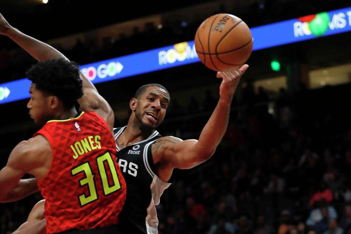 San Antonio Spurs forward LaMarcus Aldridge (12) reaches for a rebound against Atlanta Hawks center Damian Jones (30) in the first half of an NBA basketball game Tuesday, Nov. 5, 2019, in Atlanta. (AP Photo/John Bazemore)