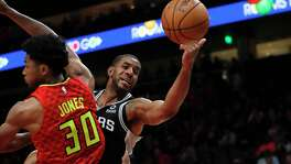 San Antonio Spurs head coach Gregg Popovich talks to guard Tony Parker in the second half of an NBA basketball game against the Atlanta Hawks Monday, Jan. 15, 2018, in Atlanta. The Hawks won 102-99. Atlanta Hawks guard Dennis Schroder (17) looks on in the background. (AP Photo/John Bazemore)