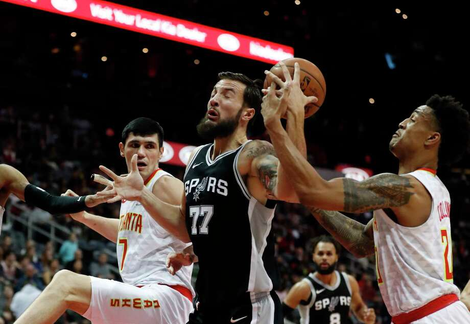 San Antonio Spurs center Joffrey Lauvergne (77) battle Atlanta Hawks forwards John Collins (20) and Ersan Ilyasova (7) as he goes in for a shot in the second half of an NBA basketball game Monday, Jan. 15, 2018, in Atlanta. The Hawks won 102-99. (AP Photo/John Bazemore) Photo: John Bazemore, Associated Press / Copyright 2018 The Associated Press. All rights reserved.