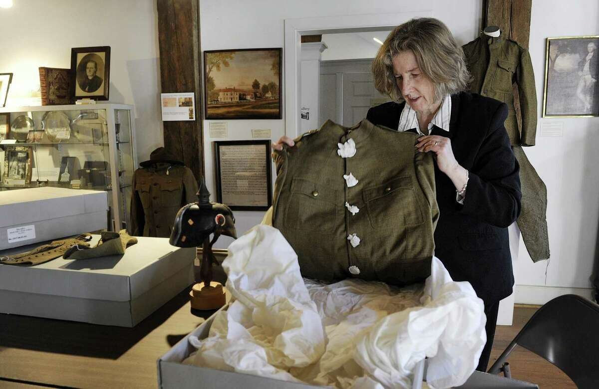 Museum assistant Kathleen Zuris takes an American Army uniform worn in World War I from it's protective boxing, Friday, Dec. 30, 2016. The New Milford Historical Society and Museum is preparing an exhibit of World War I memoribilia and artifacts.