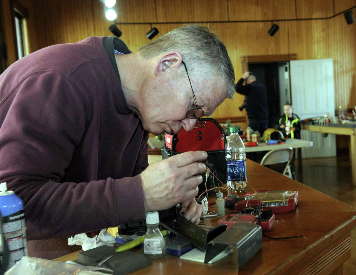 Jim Hamill of New Milford, a volunteer assisting with the train display at the old New Milford train station, repairs a 1938 Lionel whistle tender, Friday, Dec. 30, 2016.