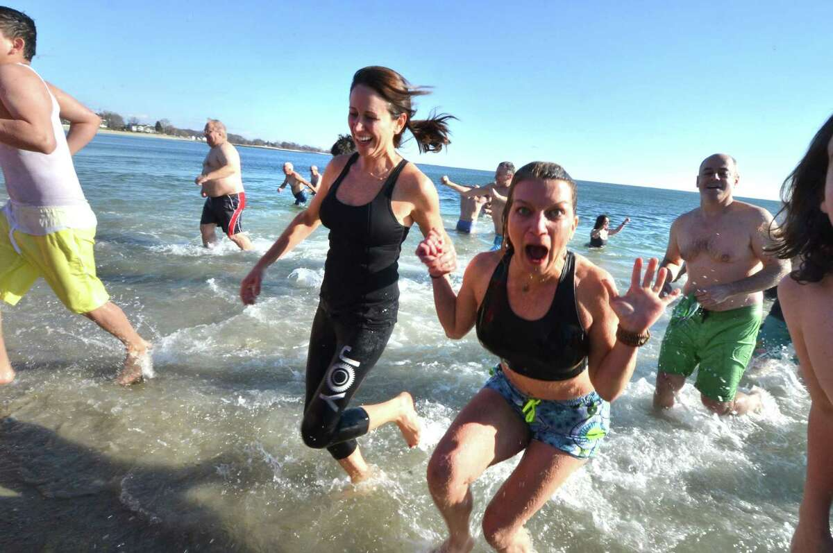 Above, Marni Lane and Rhodie Lenz, from Westport, run out of the water after a jump into a cold Long Island Sound on New Year's Day at Compo Beach in Westport during the 2017 Temple Israel 10th Anniversary Polar Bear Plunge. Around 100 people took the plunge and have raised, so far, $56,000 for many different charities, including Interfaith Housing, Marfan Foundation, Autism Speaks, PanCan, Hole in the Wall Gang, Make a Wish, and United Cerebral Palsy.