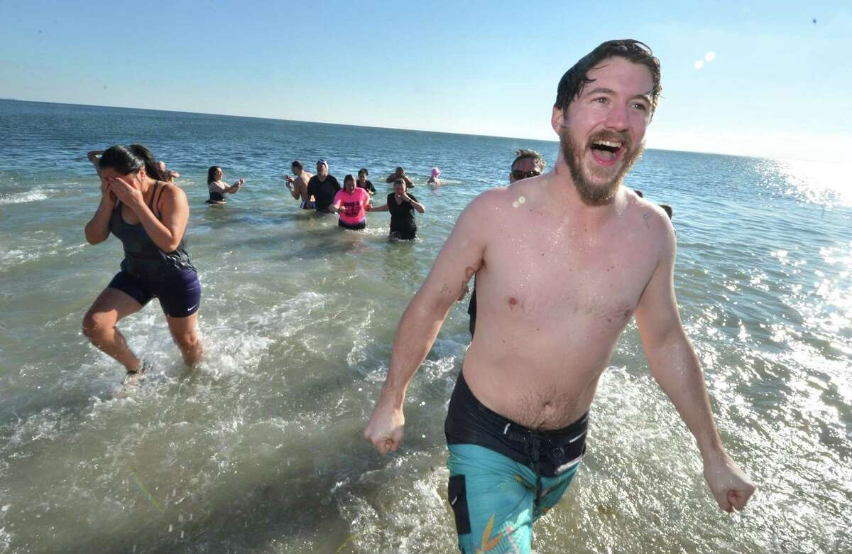 Weston's Owen Wiseman smiles after taking a dip in a cold Long Island Sound on New Year's Day at Compo Beach in Westport during the 2017 Temple Israel 10th Anniversary Polar Bear Plunge. Below, Brian