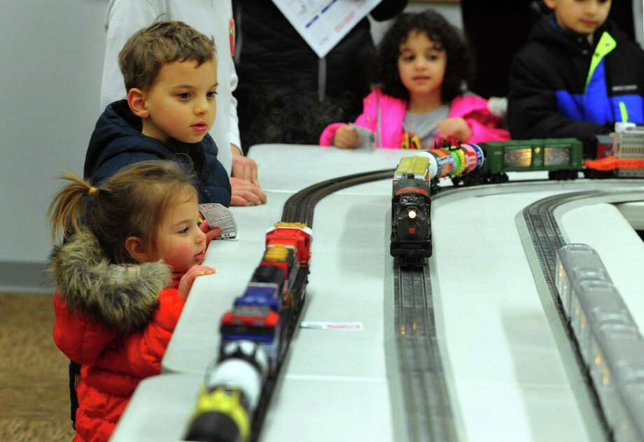 Emma Hudes, 2, of Fairfield, and her brother Zach, 5, watch the trains go by at Dennis The Train Man's O scale train display at the Westport Public Library during the 23rd First Night Westport 2017 New Year's Eve celebration in Westport, Conn., on Saturday December 31, 2016. Festivities began at 3 p.m. and ended at 10:00 p.m. In between, dozens of activities were held for people of all ages. Some of the highlights held at locations all over town were a warming fire, various musical groups, a model train display, horse drawn carriage rides and a fireworks display. Photo: Christian Abraham / Hearst Connecticut Media / Connecticut Post