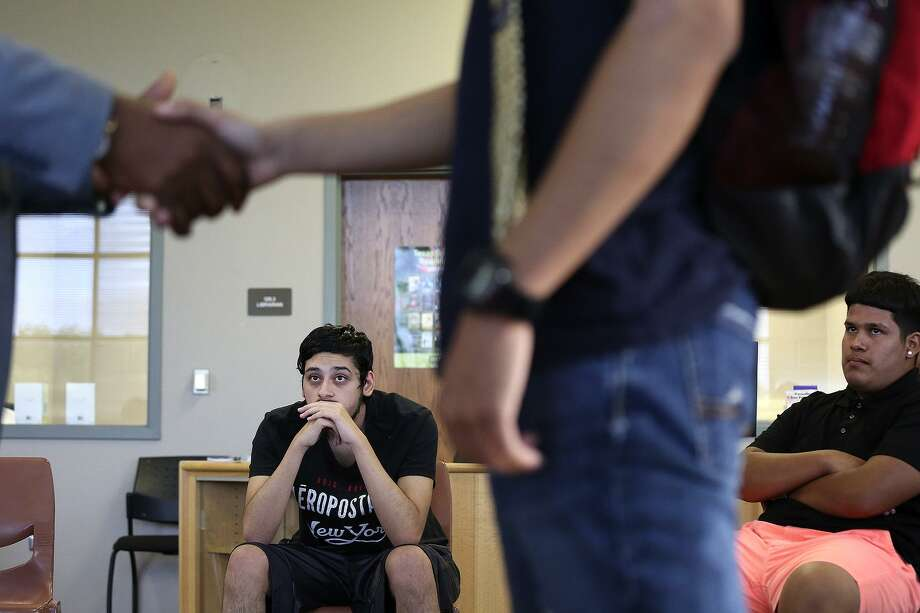 Joshua Miranda, 17 (left), and Alex Aguirre, 16, watch how to shake hands and introduce. Photo: Lisa Krantz /SAN ANTONIO EXPRESS-NEWS / SAN ANTONIO EXPRESS-NEWS